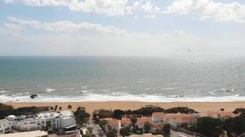 Panoramic scenic calm ocean shore with flying seagulls in Albufeira, Algarve - Pan aerial shot