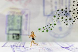 Miniature people running away from coronavirus 2019-nCoV flu infection, health crisis concept photo