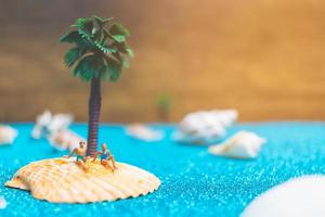 Miniature people wearing swimsuits relaxing on a seashell with a glitter background photo