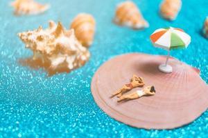 Gente en miniatura vistiendo trajes de baño relajándose en una concha con un fondo brillante foto