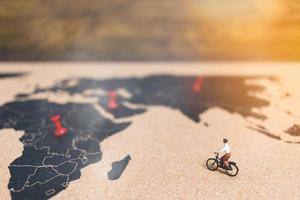 Viajeros en miniatura en bicicleta en un mapa del mundo, viajando y explorando el concepto del mundo foto