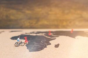 Miniature travelers riding bicycles on a world map, traveling and exploring the world concept