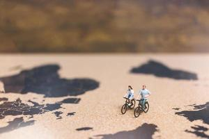 Miniature travelers riding bicycles on a world map, traveling and exploring the world concept photo