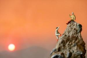 Miniature hikers climbing up on a rock, sports and leisure concept