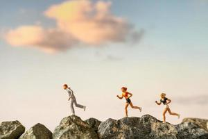 Miniature people running on a rock cliff with nature background, health and lifestyle concept photo
