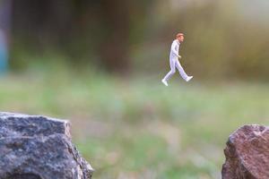 Gente en miniatura corriendo sobre un acantilado de roca con fondo de naturaleza, concepto de salud y estilo de vida foto