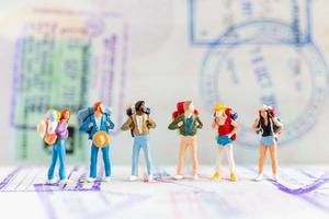 Miniature travelers with backpacks walking on a passport, travel and adventure concept photo
