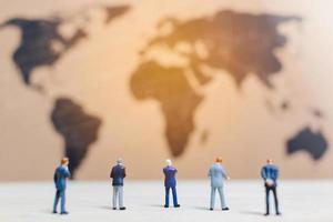 Empresarios en miniatura de pie junto a un fondo de mapa del mundo, haciendo crecer un concepto de negocio foto