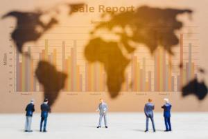 Miniature businessmen standing by a world map background, growing a business concept photo