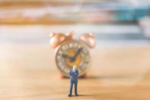 Miniature businessman standing with an old clock on a wooden background