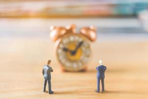 Miniature businessmen standing with an old clock on a wooden background