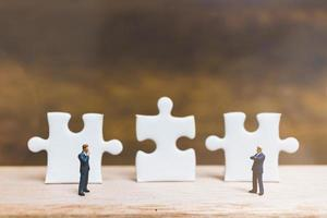 Miniature businessmen standing on jigsaws with a wooden background, business concept photo