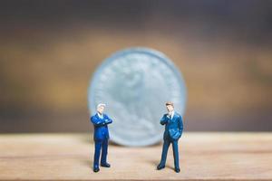 Empresarios en miniatura de pie cerca de una moneda con un fondo de madera, concepto de negocio foto