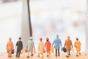 Miniature travelers walking on a wooden floor, holiday and travel concept photo