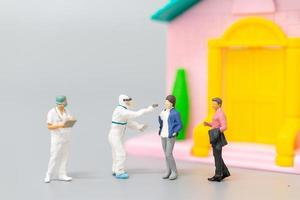 Miniature people with PPE visiting patients for a check for coronavirus at home, health care concept