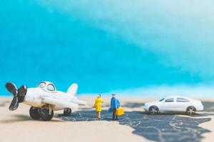 Miniature travelers with an airplane on a world map, travel and business concept photo