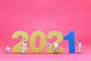 Trabajadores en miniatura pintando el número 2021, feliz año nuevo concepto foto
