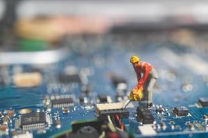 Equipo de ingenieros en miniatura que reparan una computadora portátil con teclado, concepto de reparación de computadoras foto