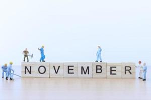 Gente en miniatura trabajando en bloques de madera con la palabra noviembre sobre un piso de madera foto