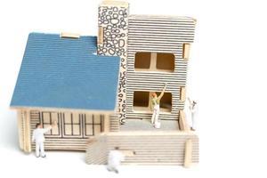 Pintores en miniatura pintando una casa de madera sobre un fondo blanco. foto
