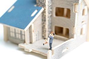 Pareja en miniatura delante de una casa de madera sobre un fondo blanco. foto