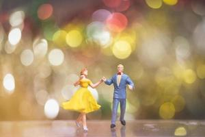 Miniature couple romantically dancing with a bokeh background, nightlife and people concept