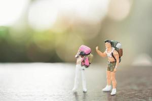 Miniature people with backpacks standing and walking, travel and adventure concept photo