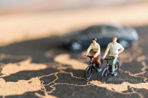 Miniature travelers with bicycles on a world map background photo