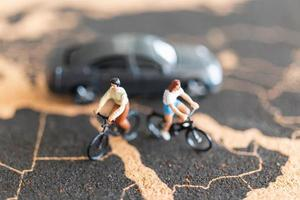 Miniature travelers with bicycles on a world map background
