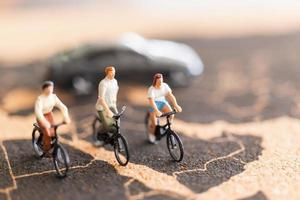 Viajeros en miniatura con bicicletas sobre un fondo de mapa del mundo foto