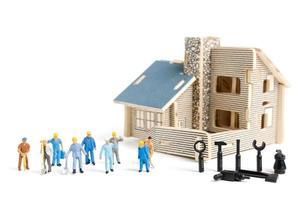 Miniature workers with tools repairing a house on a white background, construction concept photo