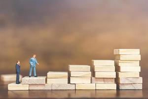 Miniature businessmen standing on wooden blocks, business career growth concept