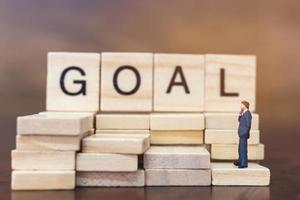 Miniature businessman standing on wooden blocks with the word Goal, business career growth concept photo