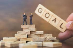Miniature businessmen standing on wooden blocks with a hand holding the word Goal, business career growth concept