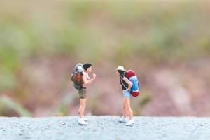 Viajeros en miniatura con mochilas de pie en un concepto de carretera, viajes y trekking foto