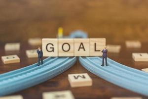 Miniature businessmen standing on wooden blocks with the word Goal, business career growth concept