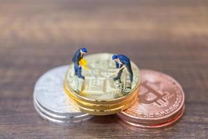 Miniature workers making Bitcoin cryptocurrency on a wooden background photo