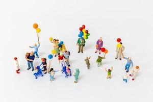 Personas en miniatura sosteniendo globos aislado sobre un fondo blanco. foto