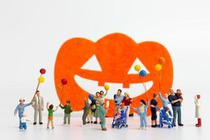 Gente en miniatura sosteniendo globos aislado sobre un fondo blanco, concepto de halloween foto