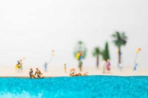 Gente en miniatura disfrutando de las vacaciones de verano en la playa. foto