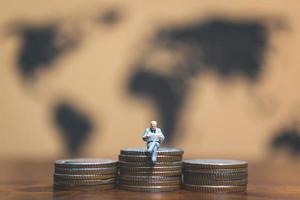 Miniature businessman on a stack of coins with a world map in the background, money and financial business success concept photo