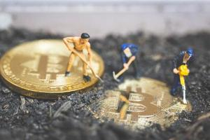Trabajadores en miniatura cavando el suelo para descubrir brillante criptomoneda bitcoin, concepto de trabajo exitoso foto
