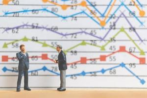 Miniature businessmen standing in front of a business graph background, business growth concept photo