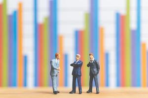 Miniature businessmen standing in front of a business graph background, business growth concept