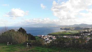 Drone footage revealing a panoramic landscape of a beautiful coastal community in Azores, Portugal.