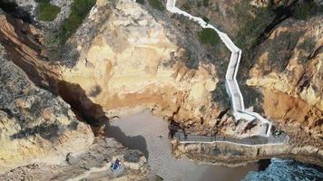 caminho em declive através da falésia rochosa até à praia paradisíaca, em carvoeiro, algarve, portugal - air push out ângulo baixo revelar foto video