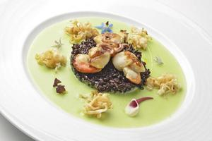 Appetizer braised scallops and black rice on pea cream photo