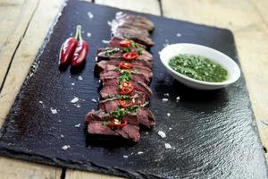 Black stone plate with skirt steak pepper and chimichurri sauce photo