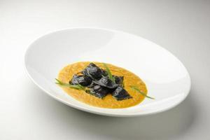 Pasta dish blacks ravioli stuffed with stockfish photo