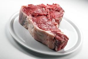 Raw T-bone steak on white round plate photo